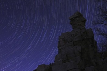 The cosmos spins and streaks behind a rock formation at Palisades State Park.
