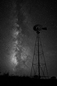 The summer Milky Way with a lone prairie windmill in a corn field of rural Brule County.