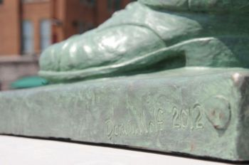 The artist's signature is scratched below Pettigrew's left shoe.