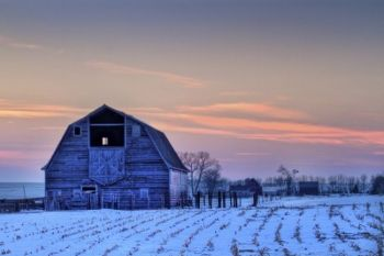 The last light of day colors the western sky with a pink hue behind this Moody County barn.