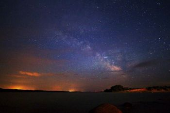 The Milky Way accompanied by clouds lit by Snake Creek campground lights and the city of Platte to the east.