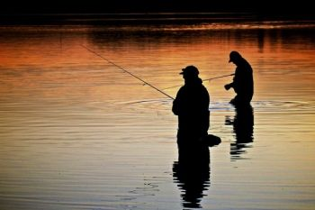 Fishermen silhouetted at sunset at Island Lake northeast of Montrose, SD.