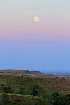 The full moon rises over the prairie hills.
