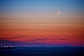 The waxing moon and comet Pan-STARRS (to the left of the moon) hang in the South Dakota sky.