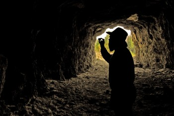 "Illustrating the mining history of the Black Hills with this photo of a prospector checking out some ore is accomplished by carefully placing a silhouette against the bright opening of a mine. Photoshop artistry later added a beard to the ""prospector"" figure."