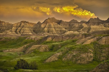 Badlands National Park glows in late evening light after a summer storm, giving the effect of a volcano erupting. Photo by Chad Coppess / S.D. Tourism.