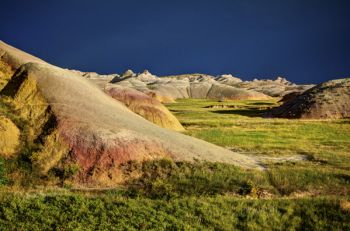 The evening sun paints the yellow mound area of the Badlands in brilliant colors with passing storm clouds as a backdrop.