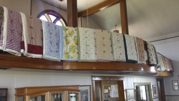 Immanuel Lutheran Church parishioners sell the quilts that line the church's balcony.