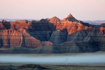 First light touching the Badlands with low fog at the foot of the formations.