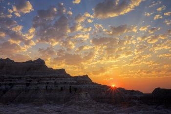 Early morning sun rays peek over Badlands formations.