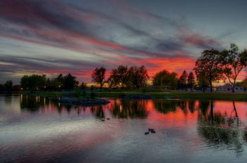 A colorful fall sunset reflected in Covell Lake in Sioux Falls.