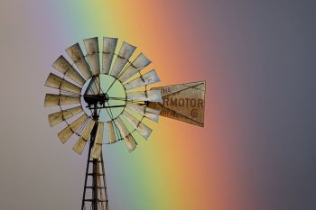 A prairie windmill with a rainbow background in rural Lincoln County.