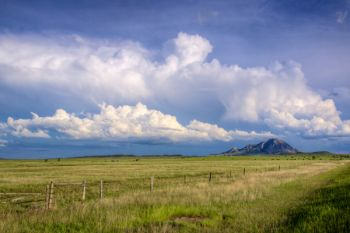 Bear Butte with distant storm clouds taken from Highway 79.
