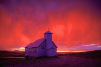 Rain colored by the setting sun above Our Lady of the Prairie Church in rural Harding County.
