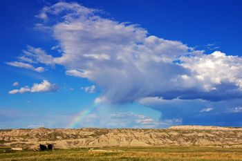 A small raincloud with a rainbow dropping over the Palmer Creek Unit of Badlands National Park.
