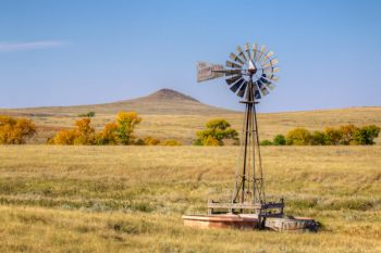 A prairie windmill with a small Harding County butte in the distance.