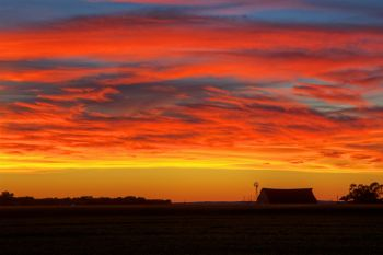 Brilliant sunset over a Bon Homme County barn and windmill.