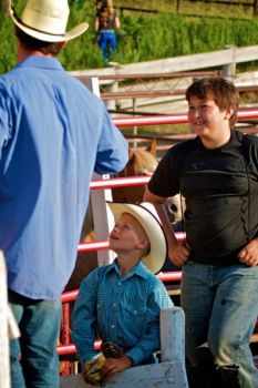 Young cowboys look up to a bareback rider just before the rodeo gets underway.