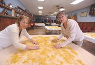 Susan Schroeder and Barb Perk turn drying noodles in Tabor s Legion Hall.