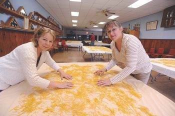 Susan Schroeder and Barb Perk turn drying noodles in Tabor's Legion Hall.