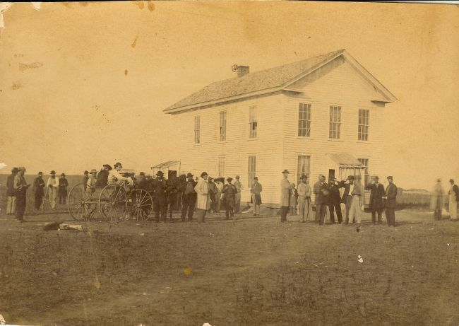 Pioneer politicians and members of the  Yankton gang  gather at the first territorial capitol in downtown Yankton.