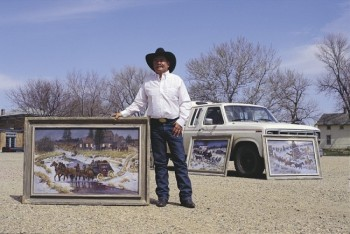Galen Wallum displays a few of the paintings he pulled out of his pickup trailer.