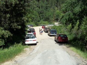 The road to Devil's Bathtub is crowded with parked cars.