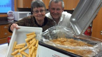 Patti Frazee (one of the kitchen helpers) with krumkake and Al Mathiasen with a roaster of klub. Photo from Kathy Mathiasen.