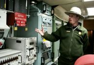 A National Park Service employee points to the double-locked red box that concealed the code and keys for a missile launch at the Minuteman Missile National Historic Site. 2007 photo by Paul Higbee.