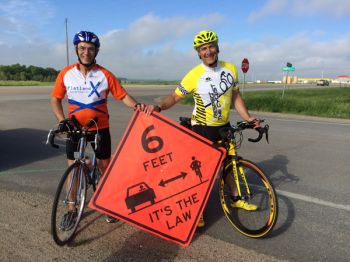 The author (left) and his legislative colleague Rep. Fred Deutsch took part in the Ride Across South Dakota (RASDAK). Their banner promotes South Dakota's new bicycling law.