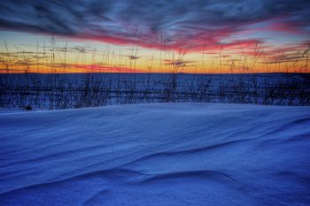 Snow on the edge of a field under a colorful post-sunset sky in Minnehaha County.
