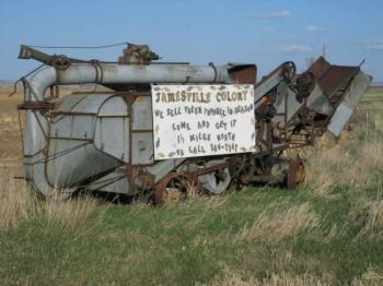 Threshing machines and other farm equipment make sturdy billboards, like this one pointing travelers to the Jamesville Hutterite Colony near Utica. Photo by Chris Moore.