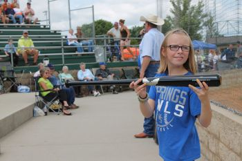 Ten-year-old Chloe Holzwarth displays the Sam Bat for the crowd while auctioneer Lanning Edwards takes bids between games of the state amateur baseball tournament in Mitchell Saturday. Photo by Craig Wenzel/Wessington Springs True Dakotan
