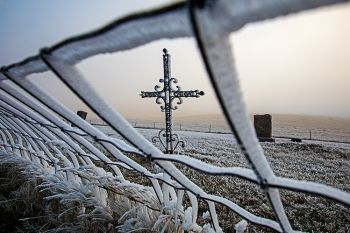 Frost and fog on an iron cross at a small cemetery south of Lowry.