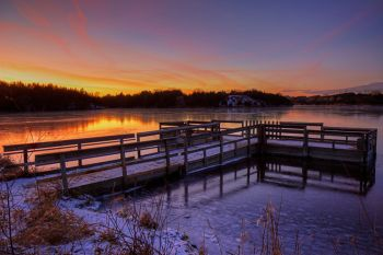 Winter sunset over the ice and fishing pier at Lake Alvin Recreation Area near Harrisburg.