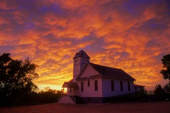Academy United Church of Christ near the Bijou Hills as the setting sun continued to color the retreating storm clouds.