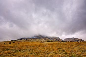 Low clouds and a light rain converge on Bear Butte.