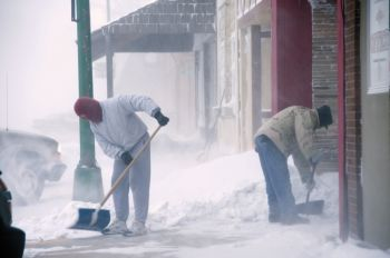 John Dangel (left) and other downtown Freeman store owners labored to keep their sidewalks open.