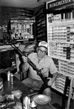Curt Carter cleans a shotgun in his small workroom. He and his son inspect every gun that they accept in trade.