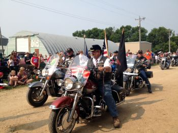 Vietnam veterans ride motorcycles through the parade.
