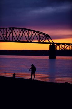 A fisherman works the shoreline between the railroad and interstate bridges at Chamberlain.