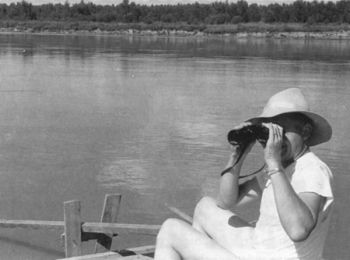 Tom Kilian takes a moment to get a closer look at the scenery along the Missouri through his binoculars.