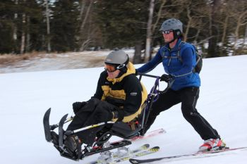 Bob Uecker, Sioux Falls, is guided by Nick Nolen, Rapid City, at Black Hills Ski for Light 2013.
