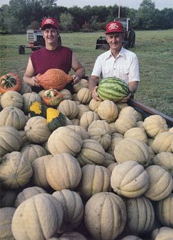 Skip and Levo Larson with a fresh crop of melons and gourds.